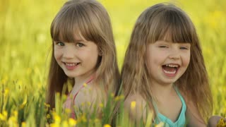 Two girls sitting in  flowers and smiling