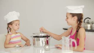 Two girls sitting in kitchen and cook