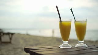 Two glasses of cocktail with straws on wooden table on the beach. People swimming in the sea in defocused background