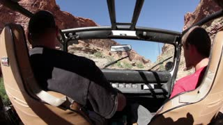 Two guys driving jeep in canyon