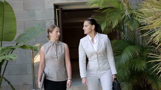 Two happy businesswoman walking in the tourist resort and talking