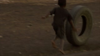 Two Kids Play with a Car Tire