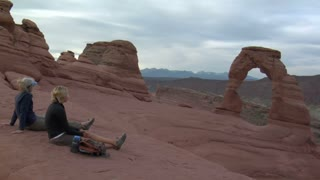 Two Ladies Sit On Rock At Delicate Arch Drinking Water