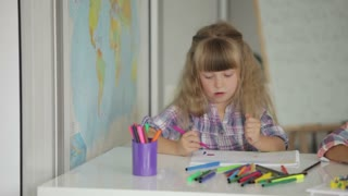 Two little girls drawing with colored pencils at drawing class and smiling at camera