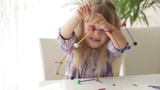Two little girls sitting at desk playing with toys and smiling at camera