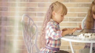 Two little girls sitting at table at cafe and using touchpads
