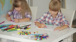 Two little girls sitting at table drawing with colored pencils and smiling at camera