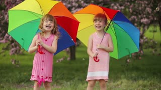 Two little girls with umbrellas laughing