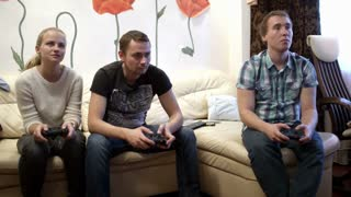 Two men and girl sitting on the sofa and playing video game using gamepads. Girl has surprising expression on the face