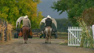 Two Men On Horses Walk By Covered Wagons
