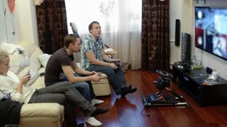 Two men sitting on the sofa at home and playing video game with gamepads, while girl using smartphone