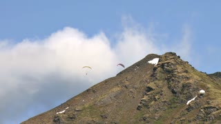 Two Paragliders Sweeping Over Mountains