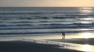Two People Walking Along Shore at Cannon Beach