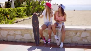 Two pretty friends hold skateboards on wall