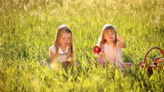 Two sisters eating apples in the meadow. Beside a basket of apples