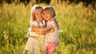 Two sisters embrace. Look at camera. They play in the meadow