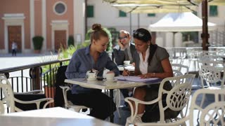 Two woman on businessmeeting sitting in cafe and talking together, outdoors