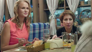 Two women dining at the restaurant and listening to the person sitting at the next table