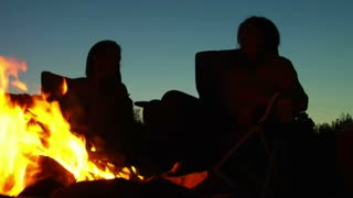 Two Women Sit Around Campfire At Dusk