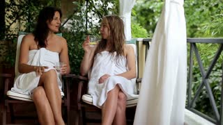 Two women talking and relaxing on balcony, steadicam shot