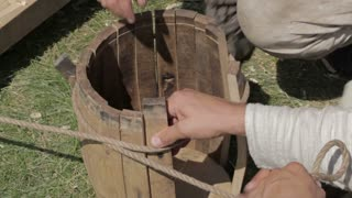 Two workers are making a barrell in a traditional style.