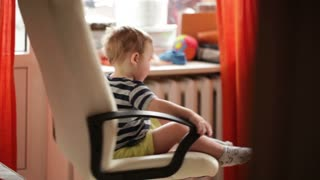 Two year old boy is spinning on chair.