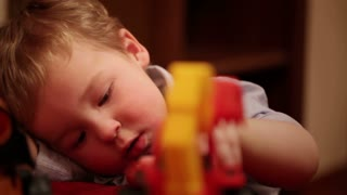 Two year old boy plays with toy trucks. Close up shot.