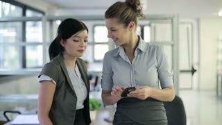Two young businesswoman enjoying smartphone in the office