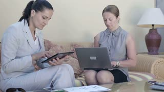 Two young businesswoman sitting in hotel lounge with laptop and tablet