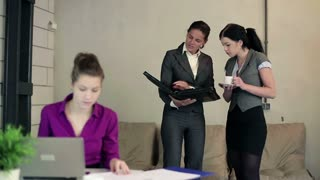 Two young businesswomen with documents in the office
