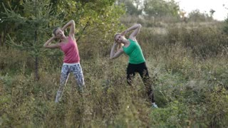 Two young girls training together outdoors: body bent exercises.