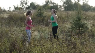 Two young girls training together outdoors: running and jumping exercises.