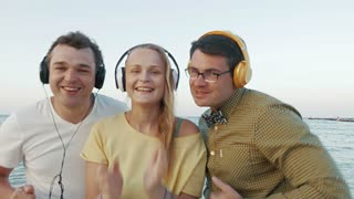 Two young men and woman dancing with music by the sea. Happy people listening favorite rhythms in headphones and getting excited