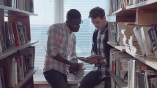 Two young men students, African-American and caucasian, sitting on window sill between bookshelves in library and talking about book, discussing literature
