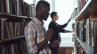 Two young men students, standing at bookshelves in library and looking for literature together