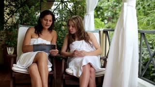 Two young woman with tablet computer relaxing on balcony, steadicam shot