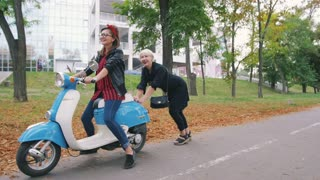 Two young women having some fun with vintage scooter in park, slow motion