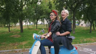 Two young women riding vintage scooter in park and having fun, slow motion