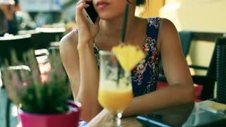Unhappy girl talking on cellphone and sitting in the street cafe