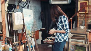 Unidentifiable female artist in studio standing in front of easel with painting in progress on it