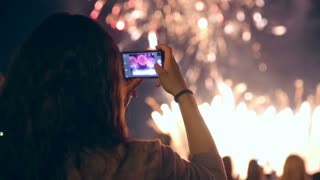 Unrecognizable woman filming colorful fireworks on his cell phone