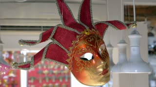 VENICE, ITALY - FEBRUARY 19, 2015: Close-up shot of bright red and golden mask hanging in store of Venetian wares