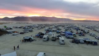 Vibrant red sunset behind Burning Man festival RVs and tents