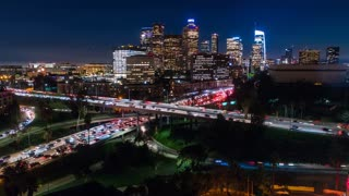 Cinematic urban aerial drone time lapse in motion of downtown Los Angeles freeways with heavy traffic, city skyline and sky scrapers at night with deep blue sky.