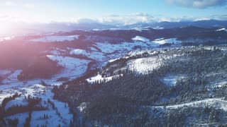 4K Aerial Drone View: Flight over Ski resort in winter. Bright colorful sunset. Mountain range with pine tree forest around. Majestic nature landscape. Bukovel, Carpathian Mountains, Ukraine