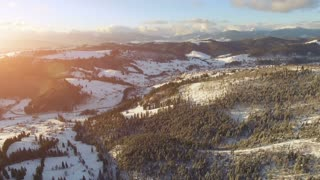 4K Aerial Drone View: Flight over Ski resort in winter, sunset time. Houses and hotels along the road. Pine tree forest around. Majestic nature landscape. Bukovel, Carpathian Mountains, Ukraine