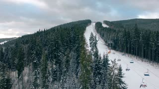 4K Aerial Drone View: Flight over winter mountains in the snowfall. Ski slopes with pine tree forest around. Majestic nature landscape. Holidays in Ski Resort Bukovel, Carpathian Mountains, Ukraine