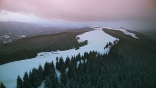 4K Aerial Drone View: Flight over winter mountains, sunset time. Ski slope, pine tree forest in the background. Majestic nature landscape. Holidays in Ski Resort Bukovel, Carpathian Mountains, Ukraine