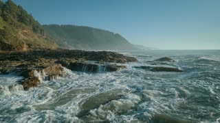 4K Aerial Flying Over Rocky Ocean Shore as Wave Splashes into Camera