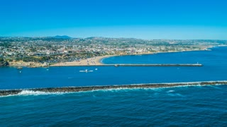 4K Aerial footage from a drone over Newport Beach harbor entrance with blue skies towards Corona Del Mar with the Pacific Ocean, beach and tourists during the Summer with coastal homes in background.